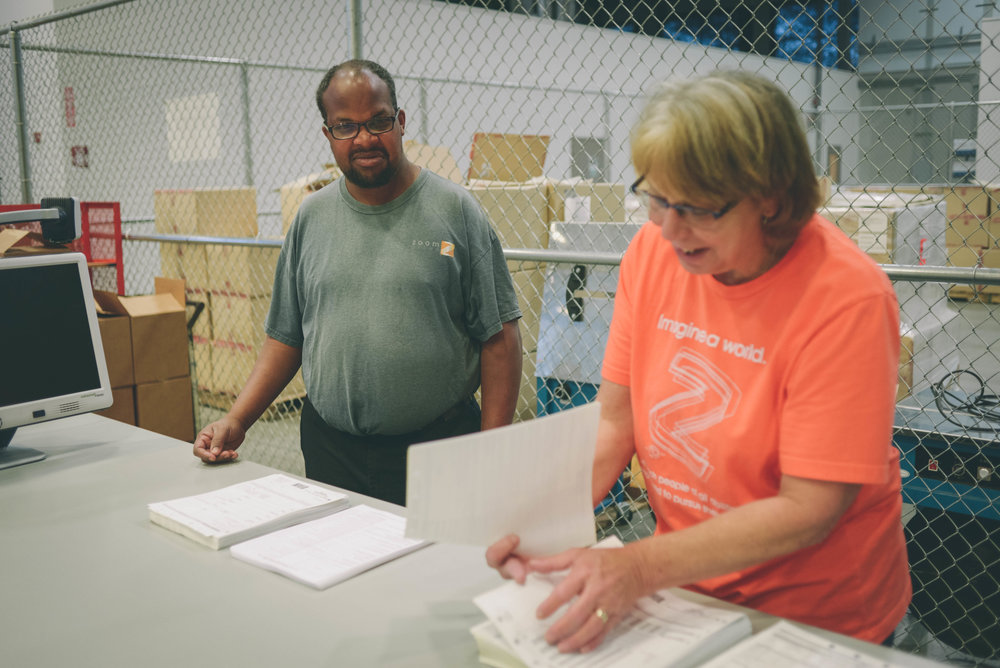 Image of two individuals in a warehouse setting. One looks on at the other sorting through some paper.