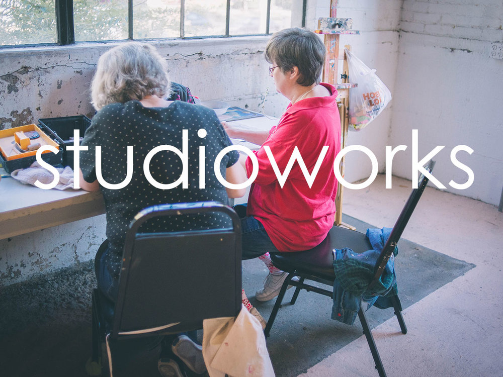 Image of two people at a table, working together on an art project. They are in a brightly lit art studio. One individual is supervising the work of the other. The word 'studioworks' is in white, overlaid on the image.