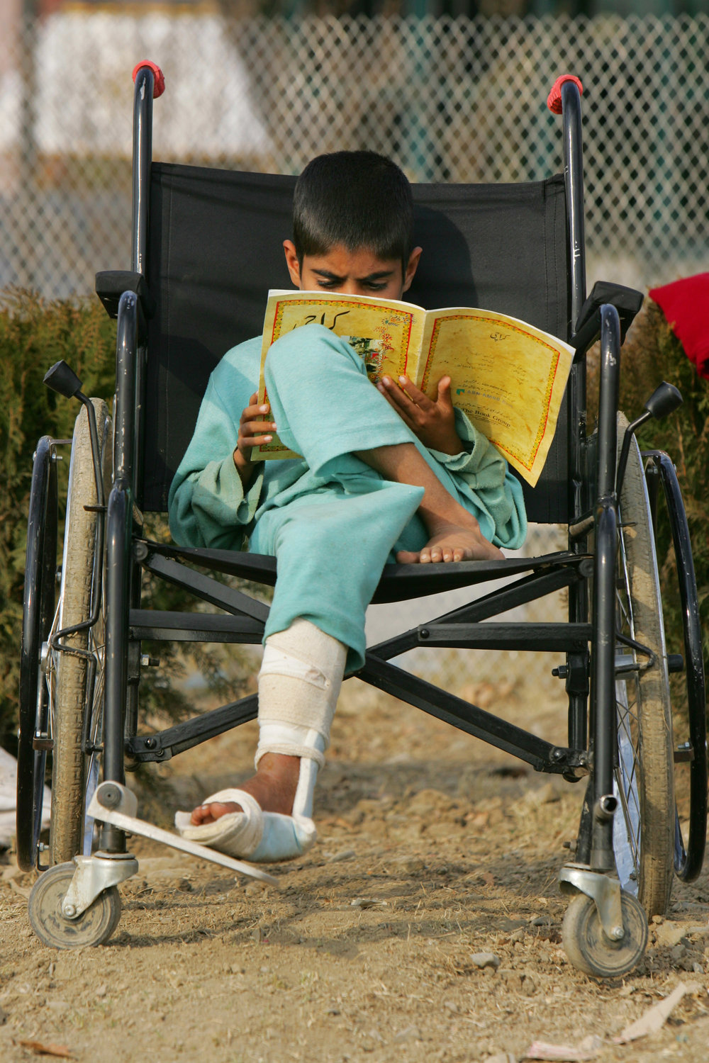 Boy in wheel chair reading a book