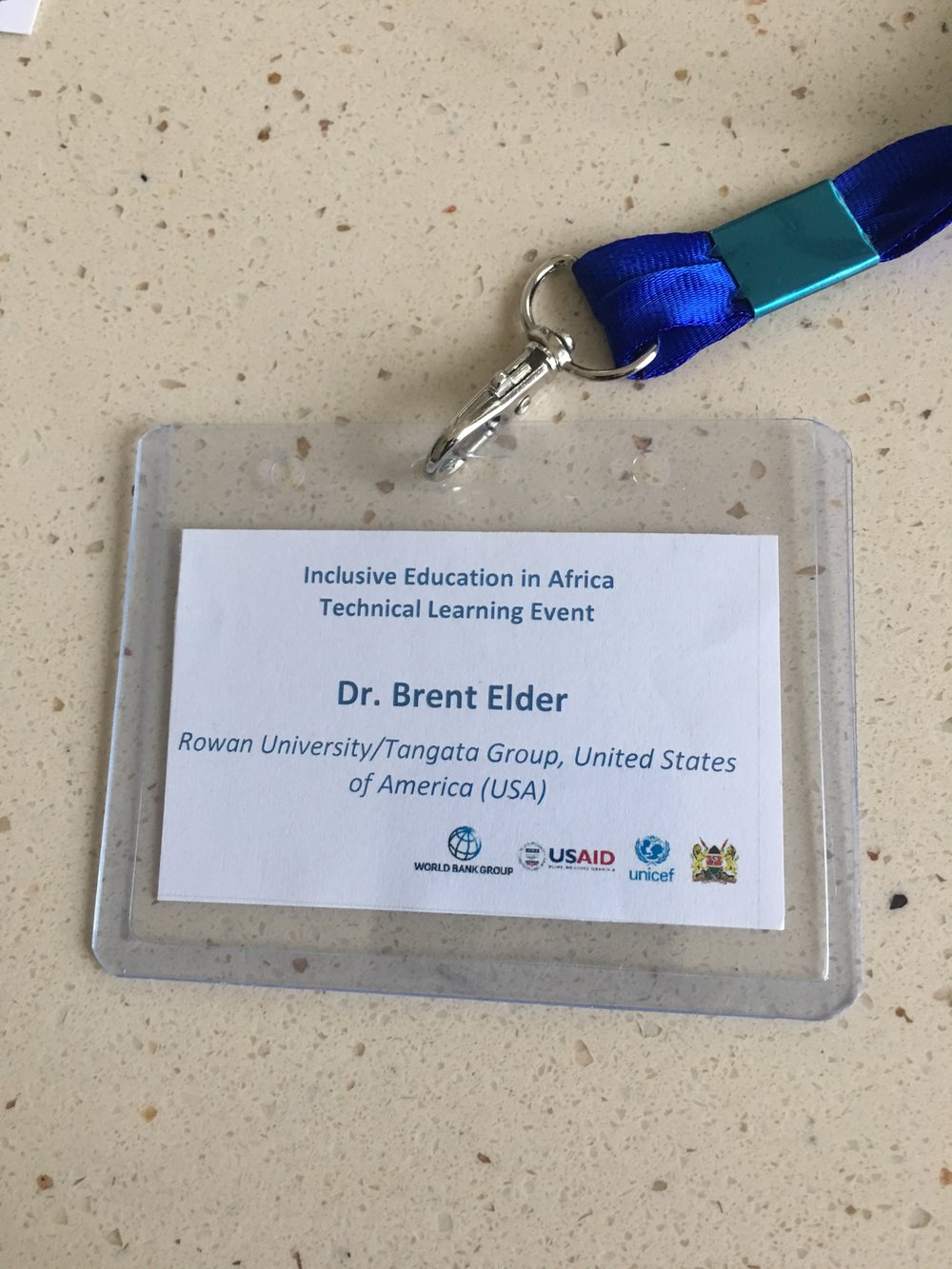 """Brent Elder's conference name tag that reads, """"Inclusive Education in Africa Inclusive Learning Event, Dr. Brent Elder, Rowan University/Tangata Group, United States of America"""" with the logos of the World Bank, USAID, UNICEF, and the Kenyan Ministry of Education."""