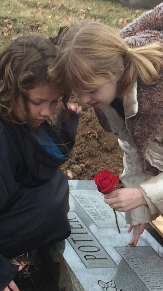 Cousins placing a rose on their great-grandfather's gravestone