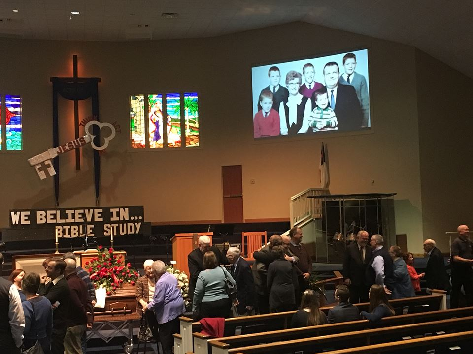 People pay their respects at Grandpa Potter's visitation, January 22, 2017, as images of his life play in the background Photo Credit: Kimberly Saunders Randall