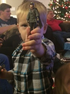 My son Micah holding his new Jyn Erso toy he got for Christmas from his great-grandpa, who is in the background on the right