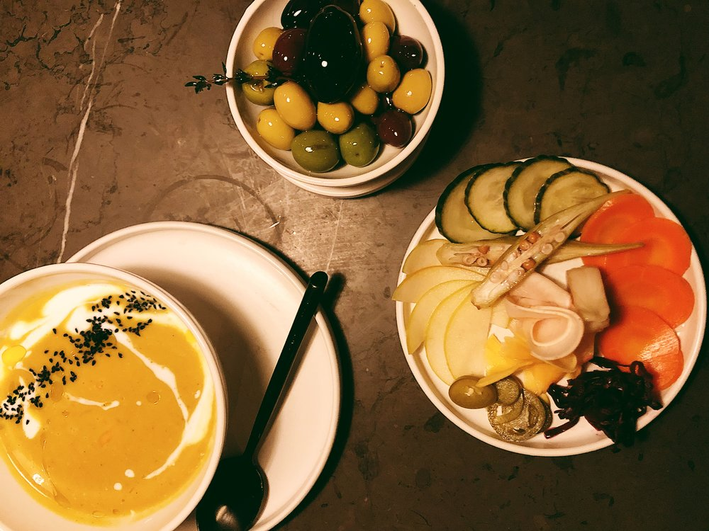 Top, from left: coconut squash soup, marinated olives and pickled pantry vegetables from Commune.