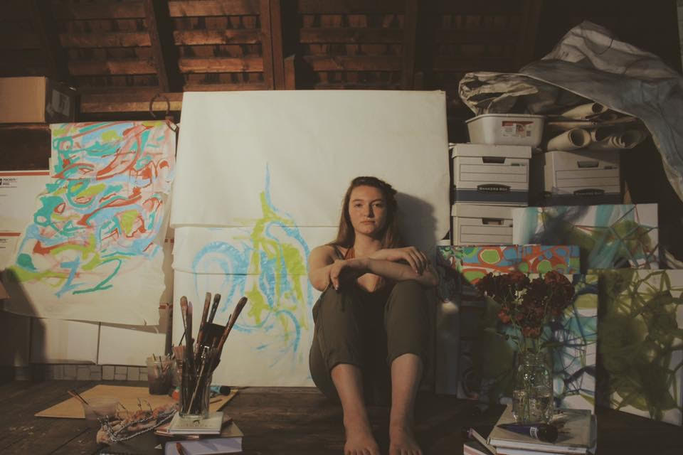 Rowan in her attic studio working on an acrylic painting.