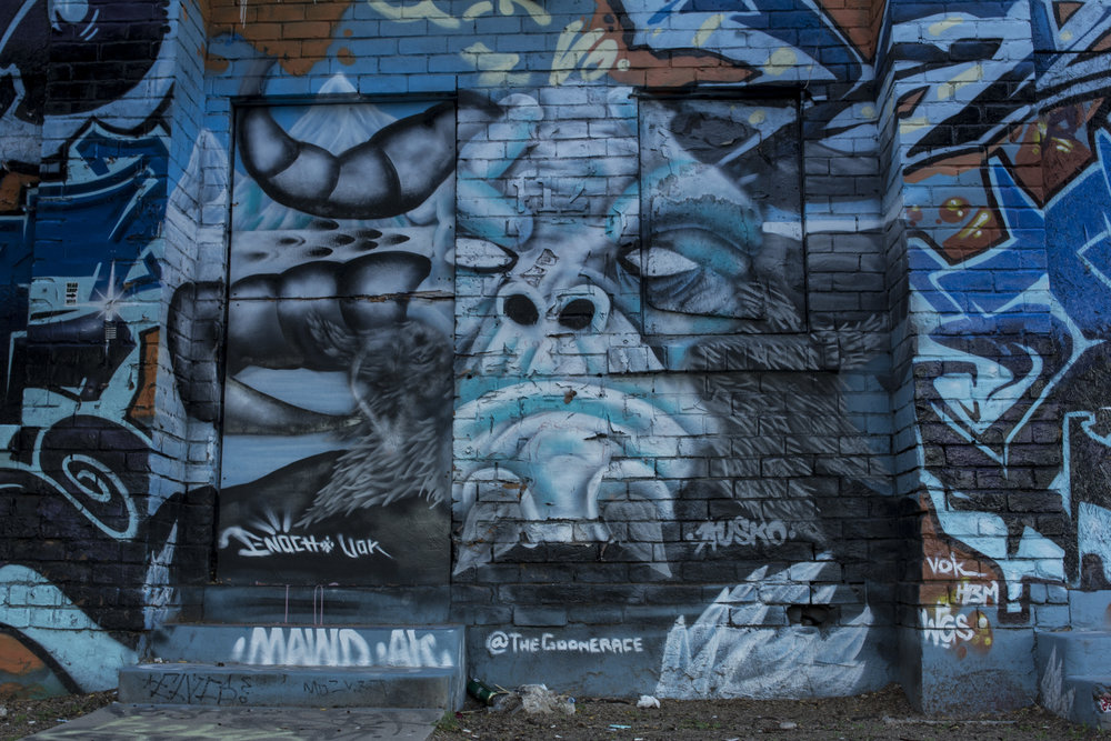 "The electric blue two-story ""graffiti altar"" behind Bliss, mural by @TheGoonERACE. Photo by Brandon Salaz."