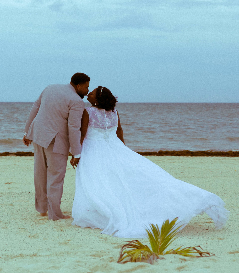 tressa-how-to-plan-a-destination-wedding-in-cancun-mexico-moon-palace-resort-black-destination-bride-destiland-desti-guide-to-destination-weddings-beach-wedding-kiss.jpg