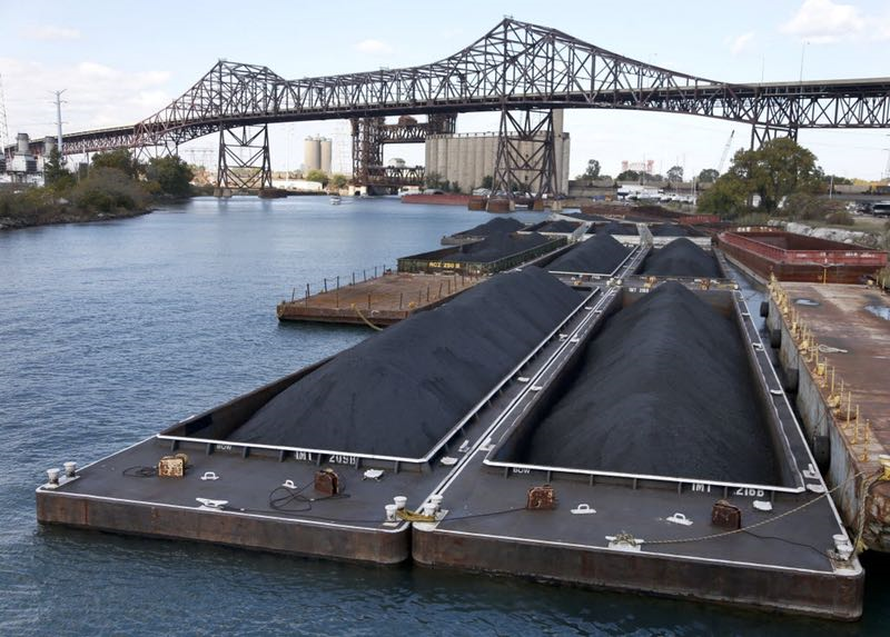 Petroleum coke, or petcoke, is stored on barges on the Calumet River near the Chicago Skyway Bridge in Chicago. (AP Photo/Charles Rex Arbogast) 11262013xNEWS   AP