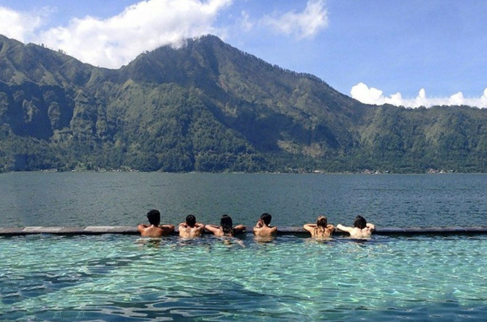 Enjoy a cocktail and relax in the gorgeous Toya Devasya Hot Springs at sunset. -