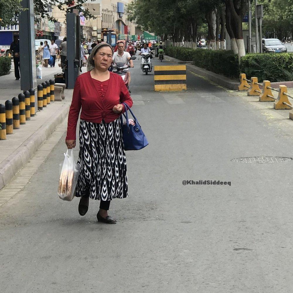 إمرأة من قومية الإيغور تضع منديلاً خفيفاً لتخفي شعرها