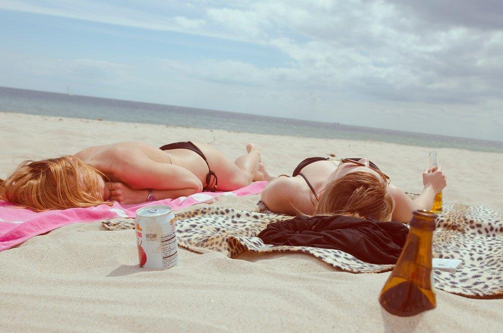 young girls sunbathing on a beach relaxing