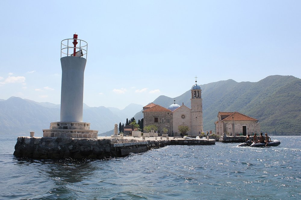 a lighthouse and a church in the middle of the sea, at Montenegro, Europe