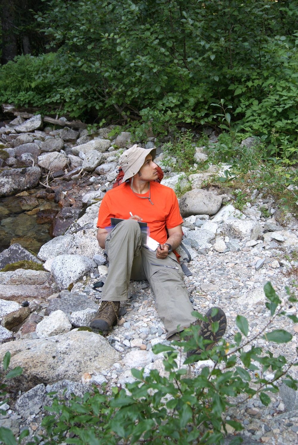 The author grinning and bearing a hike through the cascades, taking a break to write.