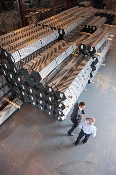 businessmen-talking-near-steel-tubing-in-warehouse-picture-id183742124.jpg