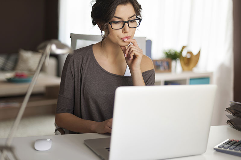 User Experience Design - Woman contemplating her website design on laptop