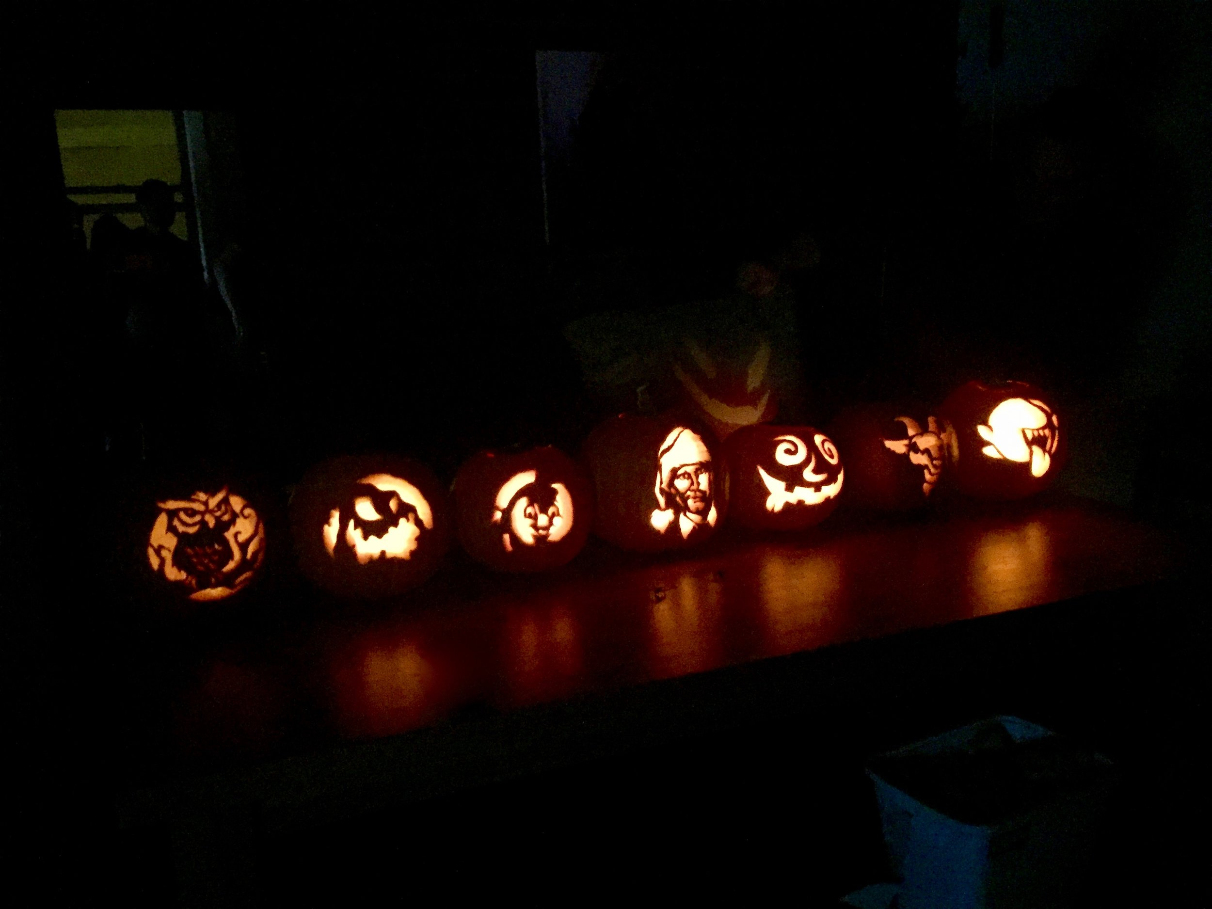 The spooky shadow behind the pumpkins.