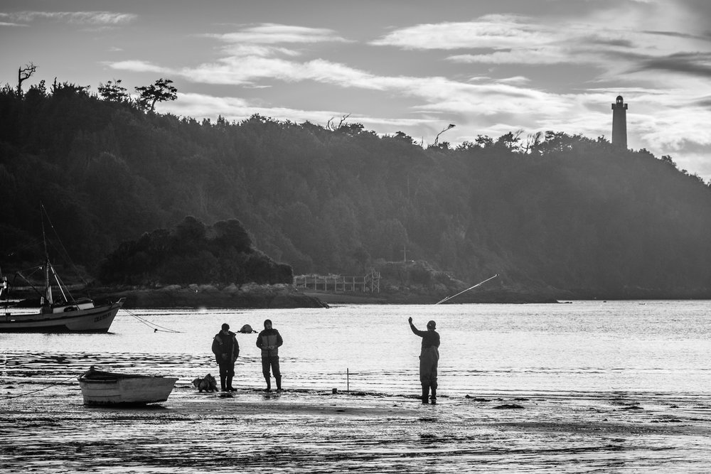 Fishermen on the beach in Inio, with the lighthouse in the background