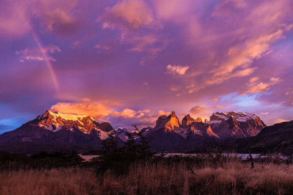 the world famous torres del paine national park - Purples, pinks, oranges and reds fill the sky during sunrise after a storm at Torres del Paine National Park.