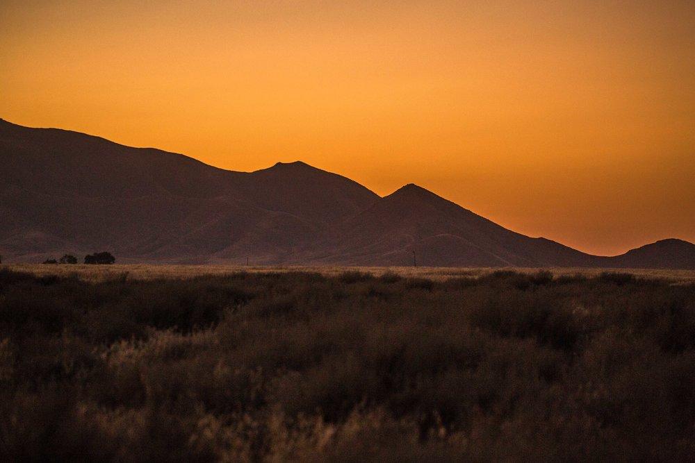 caliente ridge, carrizo plain - The sun setting behind the Caliente Range, turning the hazy sky deep orange, in California's Carrizo Plain National Monument.