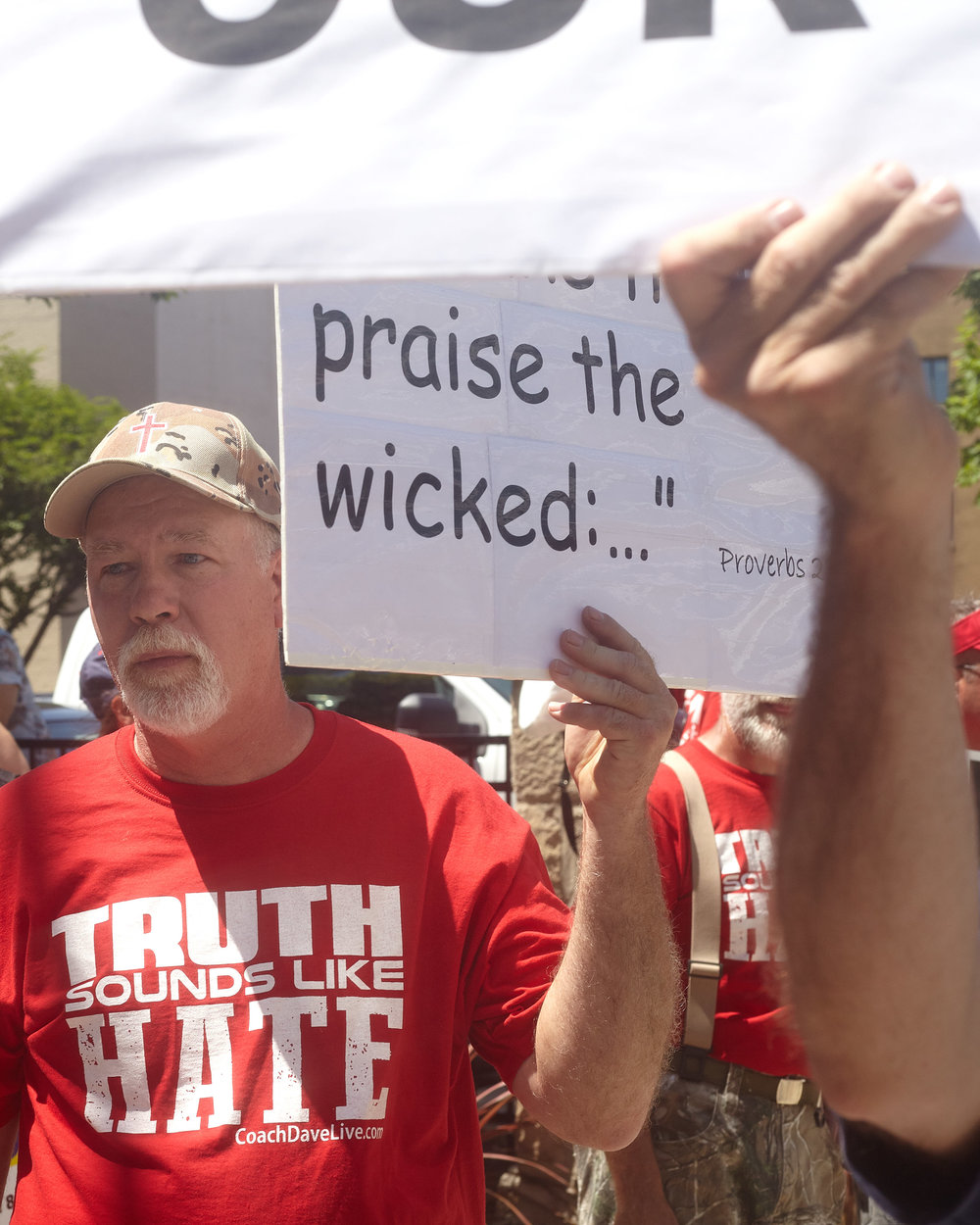 "A counter protester wearing a shirt that states ""Truth Sounds Like Hate"" holds a sign with a biblical passage."