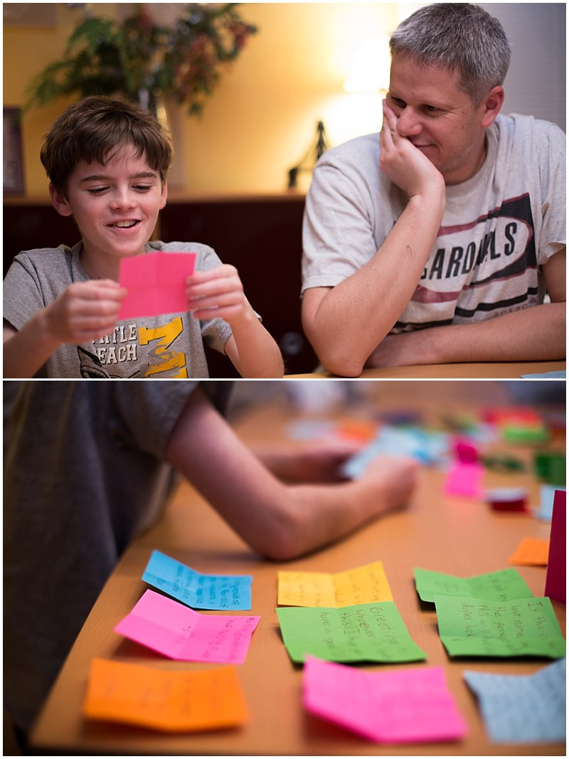 Young boy reads gratitude note while father watches.