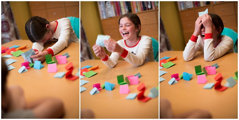 Young girl laughs at funny gratitude note.