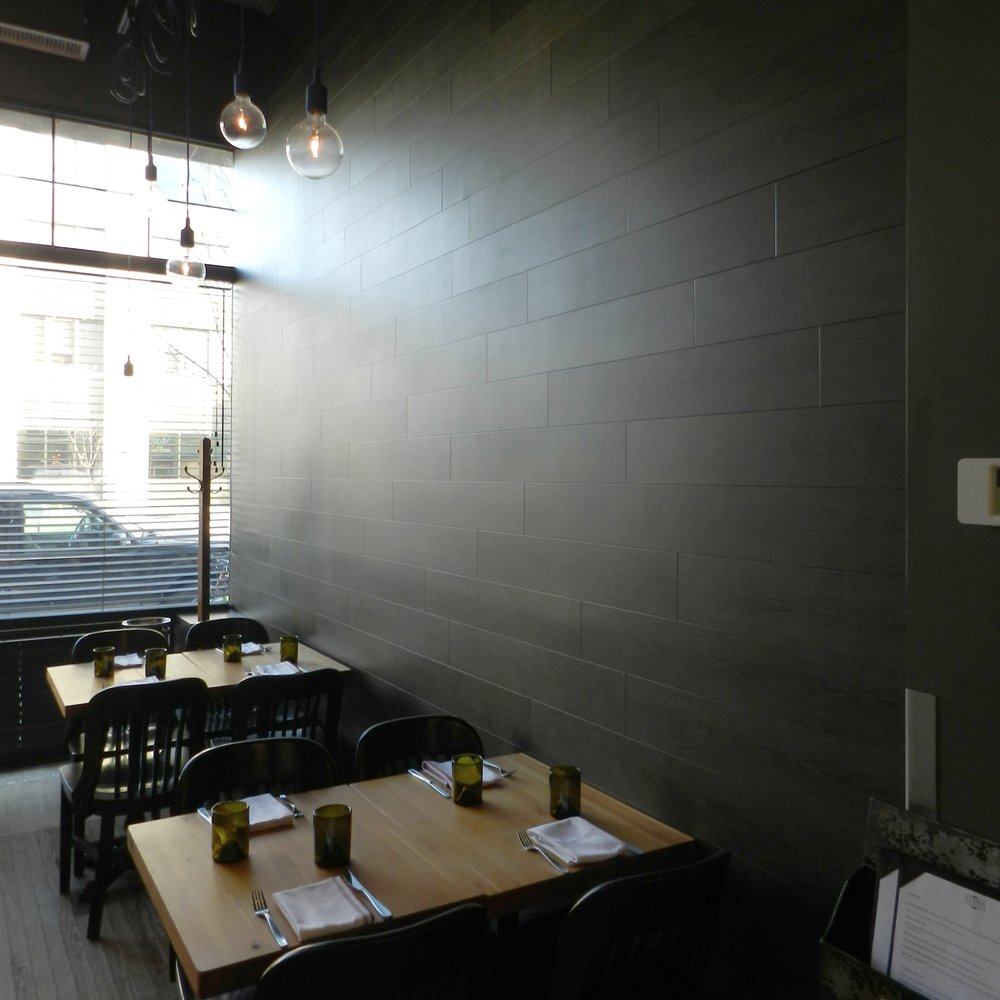 Wood look wall tile is ideal for a restaurant setting. Its a cleaner surface than wood that doesn't change its look over time, while maintaining the earthy suggestion of a wooden surface. The dark color makes the space feel intimate and edgy all at once.