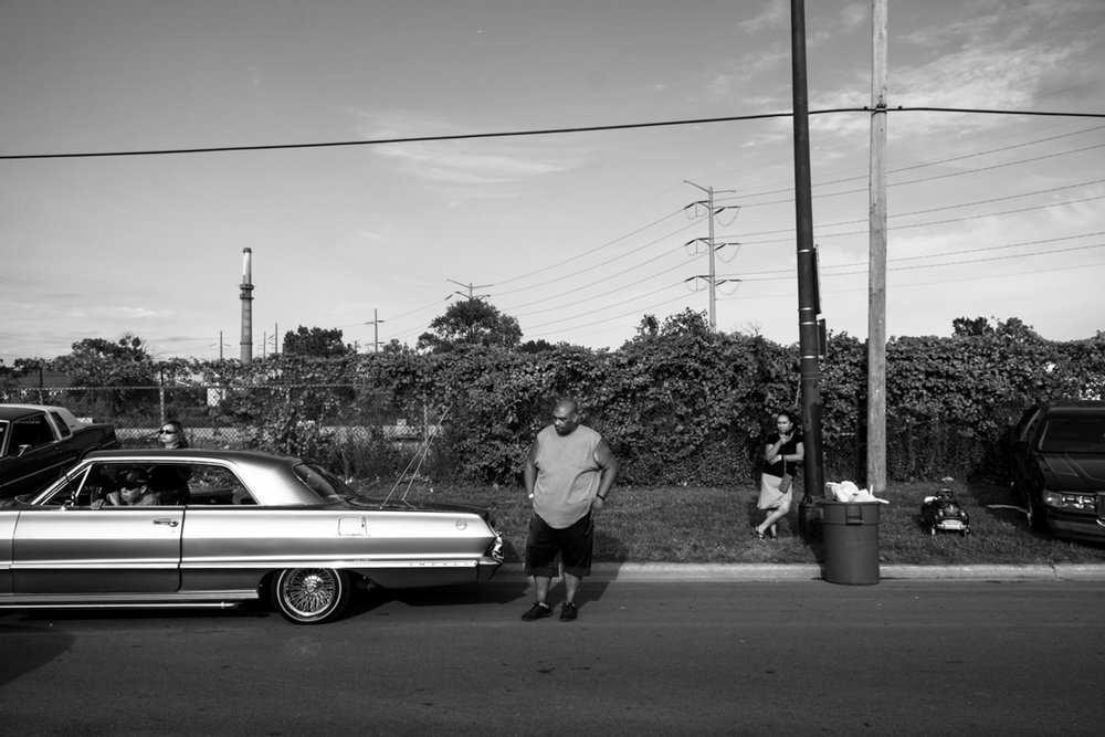 Lowrider enthusiast watch as passing cars begin to drive out the festival on Sunday, August 6, 2017, during the annual Slow and Low: Community Low-Rider festival in Pilsen.