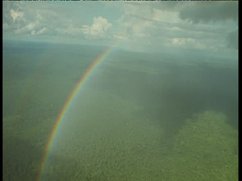 High in the sky, a rainbow arches over the amazon