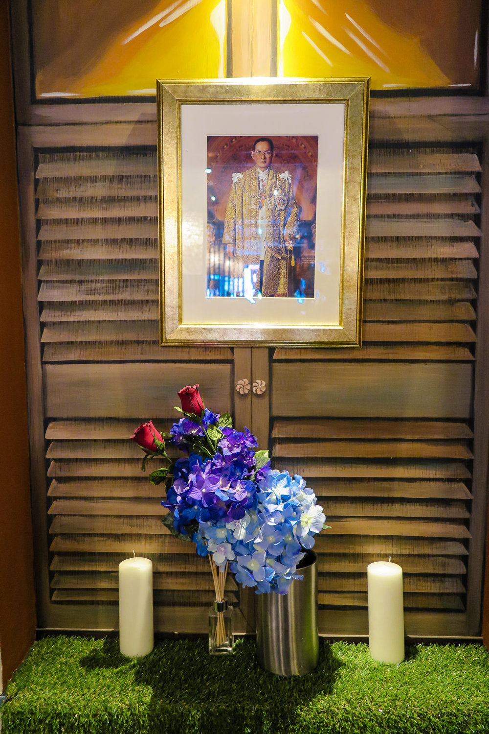 A photograph of the late Thai King Bhumibol Adulyadej. There's also a photo of the current king on the other side of the wall.