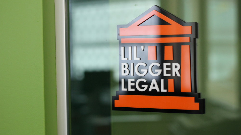 """Conference Room Sign   The Legal Team within QL needed a conference room sign for their private room. They chose the name """"Lil' Bigger Legal"""" since this was the new expanded version of their previous room """"Lil' Legal."""" Their building had bright orange and green colors, so I used orange in the sign to contrast with the surrounding green wall."""