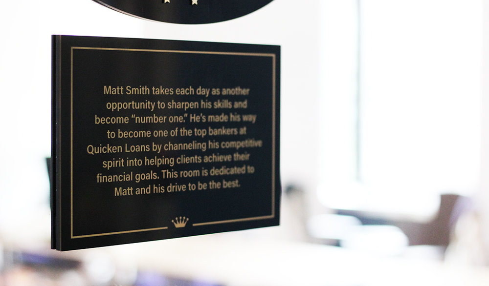 Conference Room Plaque   In order to honor the best of the best, select conference rooms are named after team members. Underneath the conference room sign rests a plaque that gives you information about the team member the room is named after.