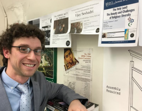 """Dr. Fazioli pictured in his office alongside posters from past """"Borders"""" and """"Time"""" Liberal Arts events."""
