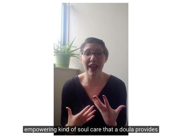"Image description: a screenshot of a Youtube video of Sarah explaining. She's mid-sentence, clearly in the middle of saying something, expressive with her hands, and sitting in front of a window with a plant. The subtitles below say, ""empowering kind of soul care that a doula provides"""