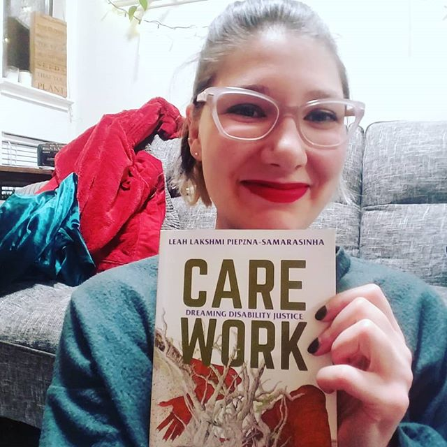 "New year, new read! This was my holiday gift from my best friend. A few essays later, already deeply moved. [Image description: sarah grinning in a relaxed apartment setting with blankets behind her, holding up a book for the camera to show off the title and author: ""Care Work: Dreaming Disability Justice,"" by Leah Lakshmi Piepzna-Samarasinha]"