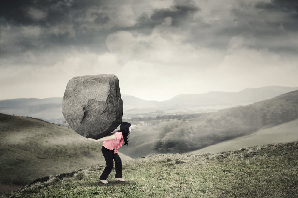 Woman carrying a rock on mountain Woman carrying a rock on mountain