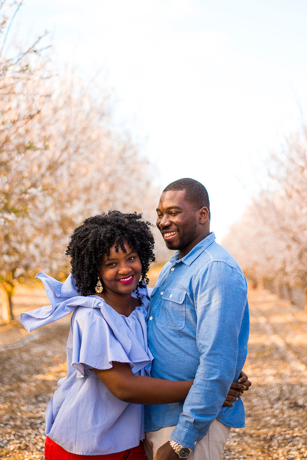 Family portrait photographed in a blossoming almond grove in Central Valley California by photographer Lillian Short.