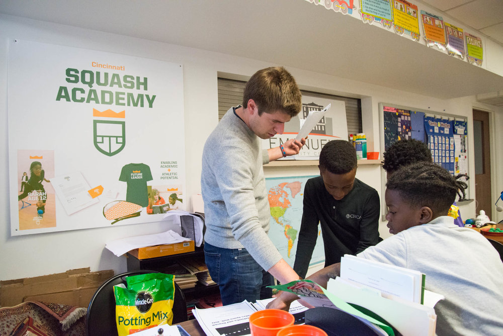 Austin Schiff, executive director of the Cincinnati Squash Academy, hands out papers and academic work to students at the Cincinnati Squash Academy. The program incorporates an emphasis on education in addition to athletics.