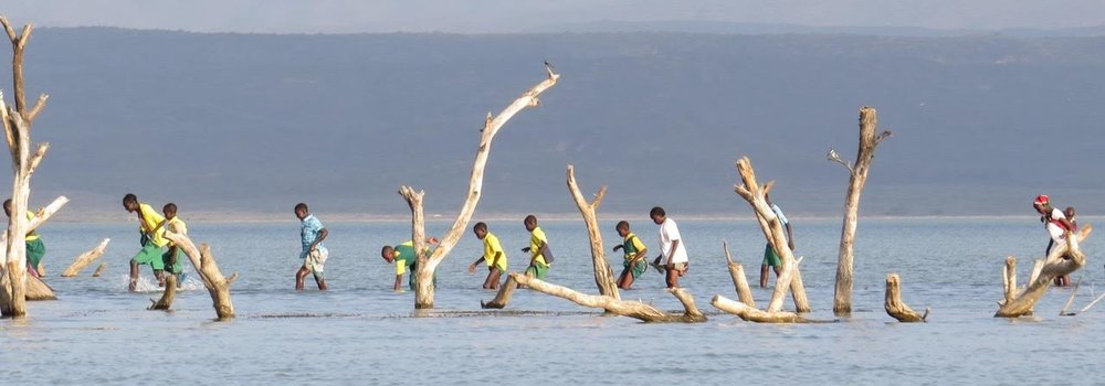 Students cross the lake on their way home from Kokwa Primary School