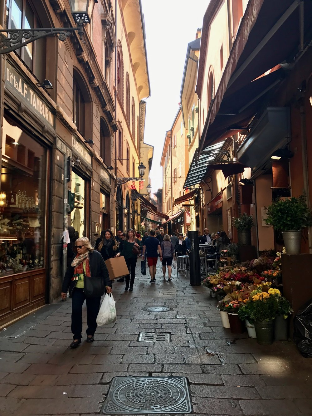 Tourists and citizens cruise through the city streets of Bologna.