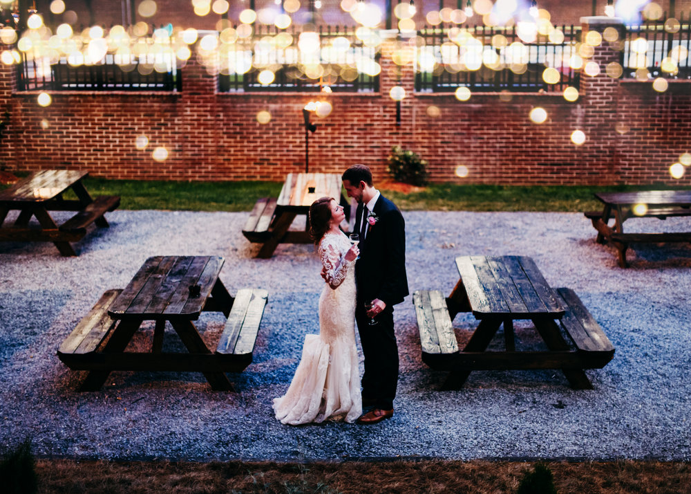 Bride and groom string lights downtown Raleigh wedding