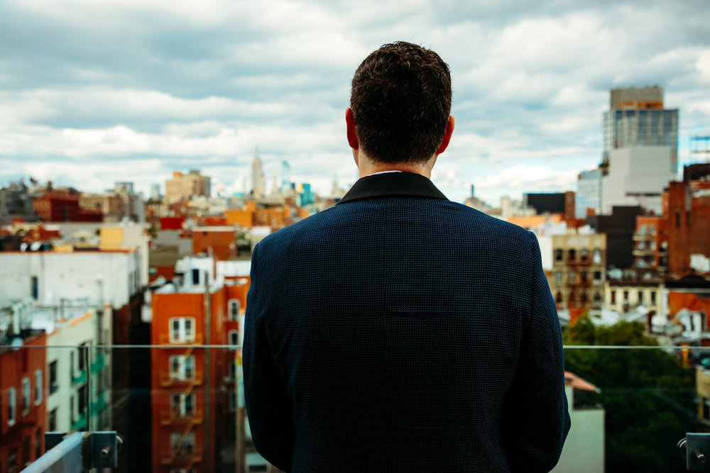 groom overlooking the city at Nolitan Hotel, Soho, New York City