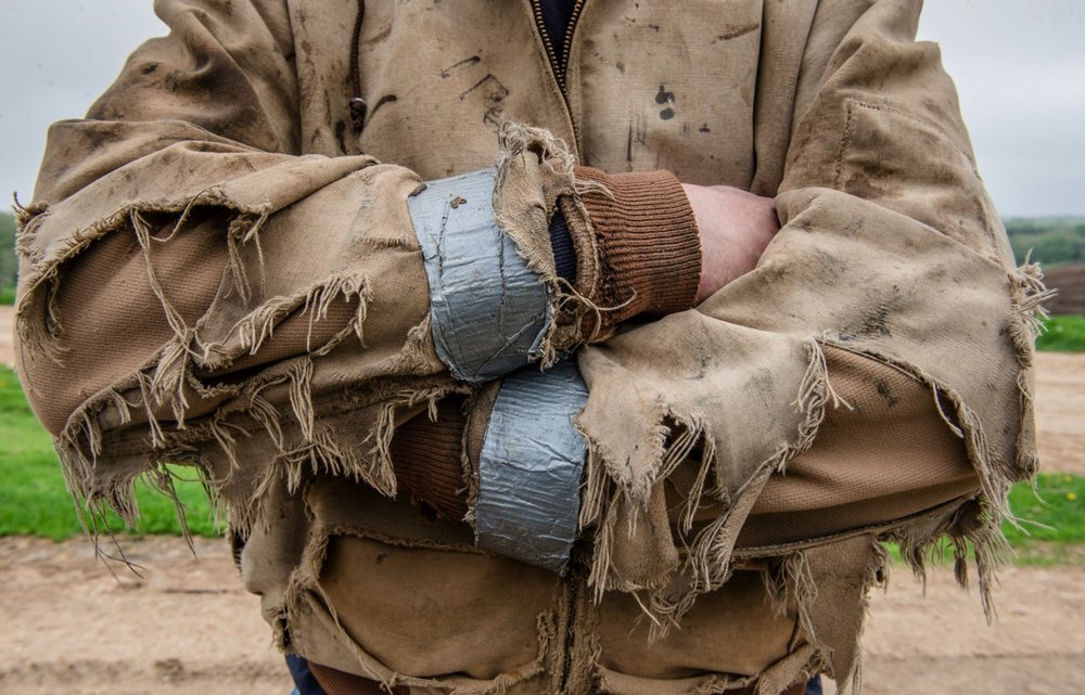 How hard do you work? Better yet can your clothes handle your job? In this case, a Carhartt jacket is tattered, torn and taped but still protecting Charlie Peters from the elements.