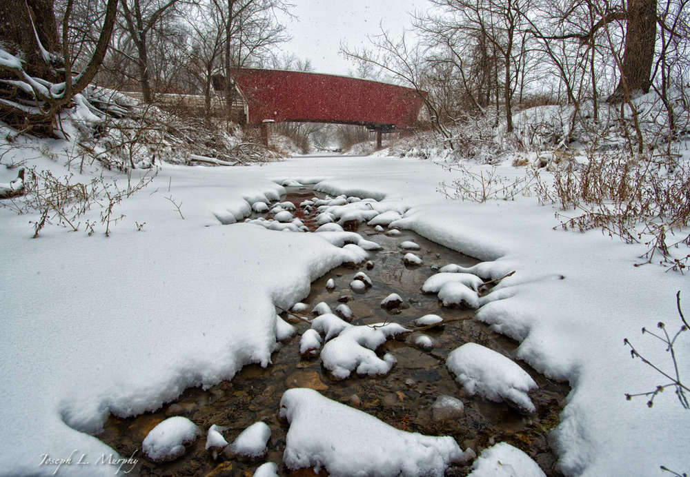 The Cedar Bridge in Madison County near Winterset, Iowa spans a snow covered creek.