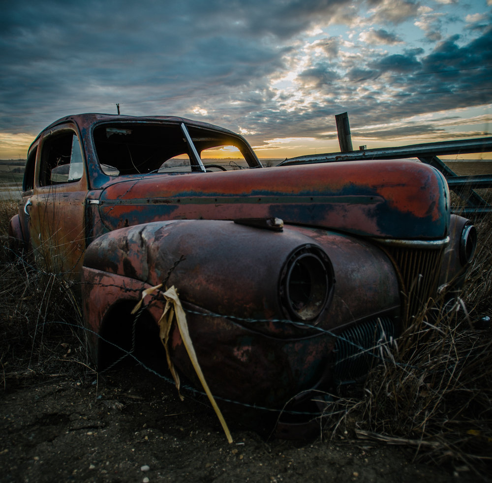 An abandoned car rests on the open prairie ground of northwest Iowa.