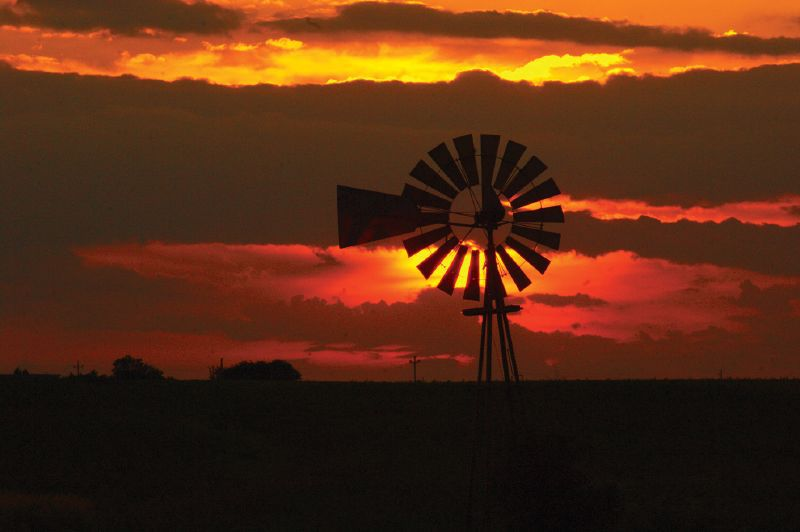 The sun sets behind a windmill in Union County south of Winterset, Iowa.