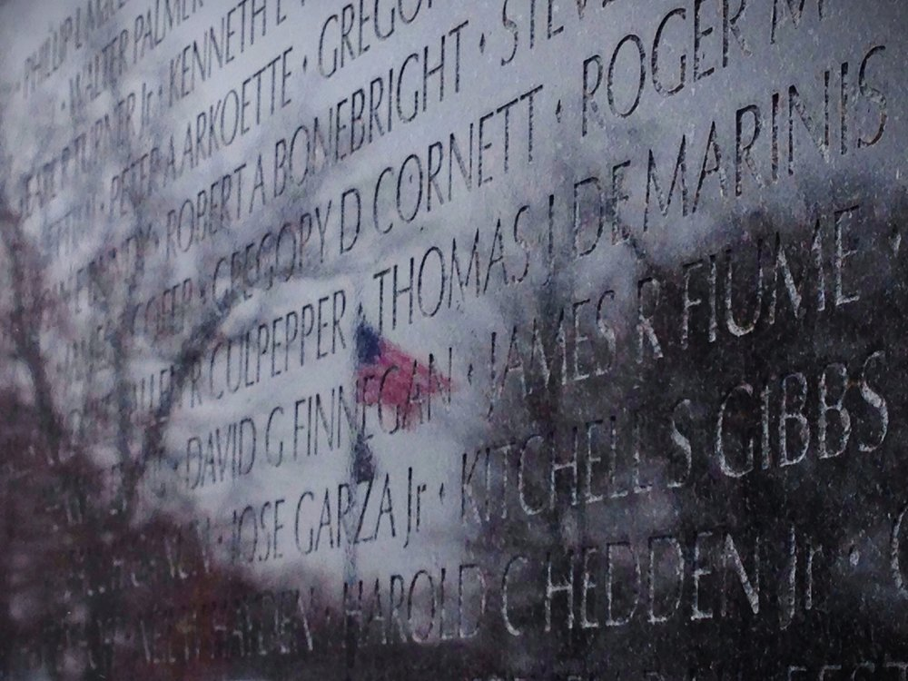 The American flag is reflected in the Vietnam Memorial in Washington, D.C.