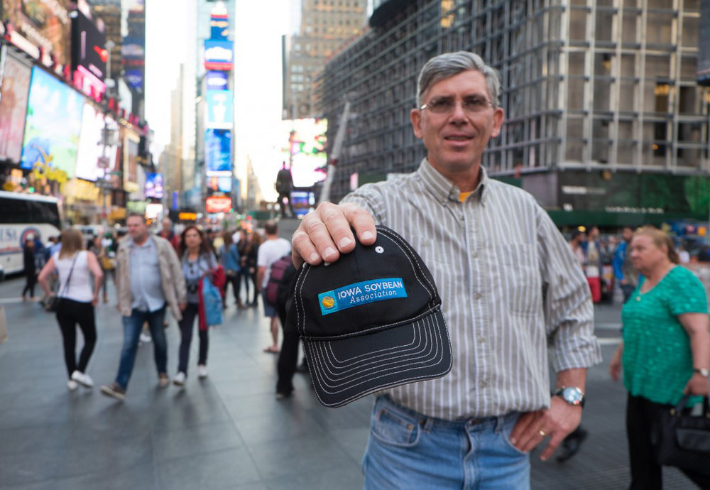 Mark Jackson holds an Iowa Soybean Association hat in Time Square in the heart of New York City.