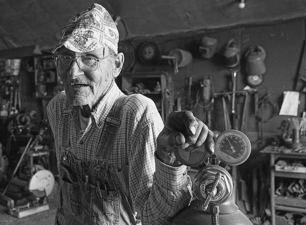 Hartford Cooper pauses for a portrait in his rural welding shop.