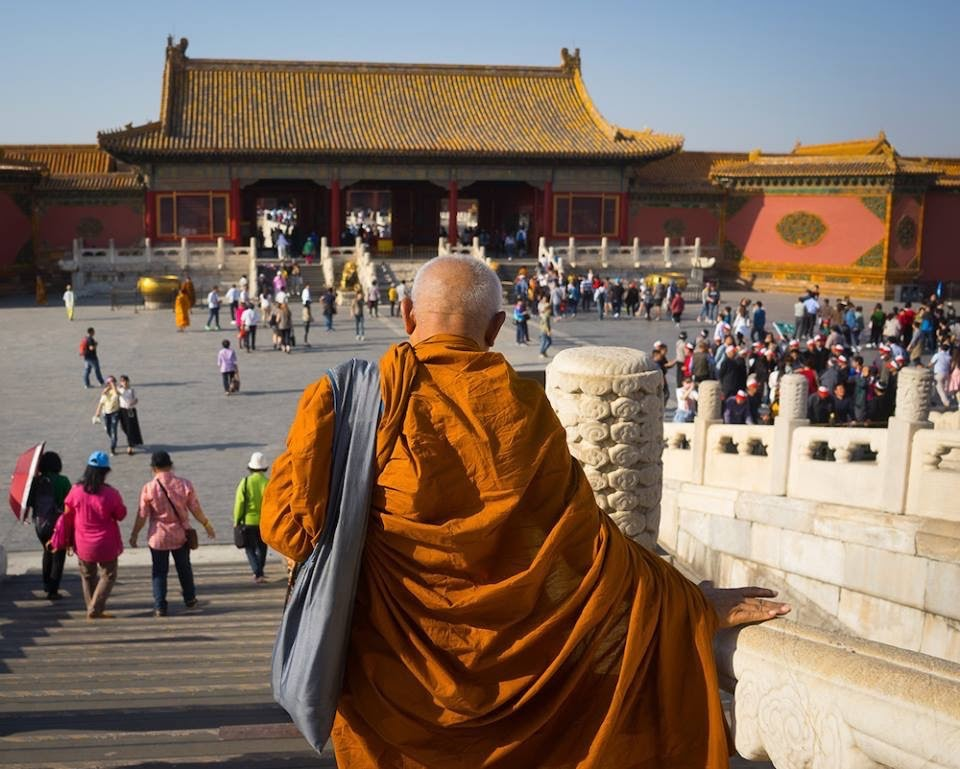 A monk walks down the stairs at the entrance of the Forbidden City in Beijing, China.